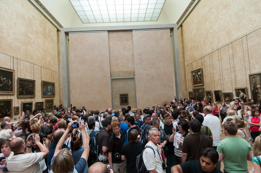 Mona Lisa fever! Crowd in front of a tiny Mona Lisa painting protected behind glass